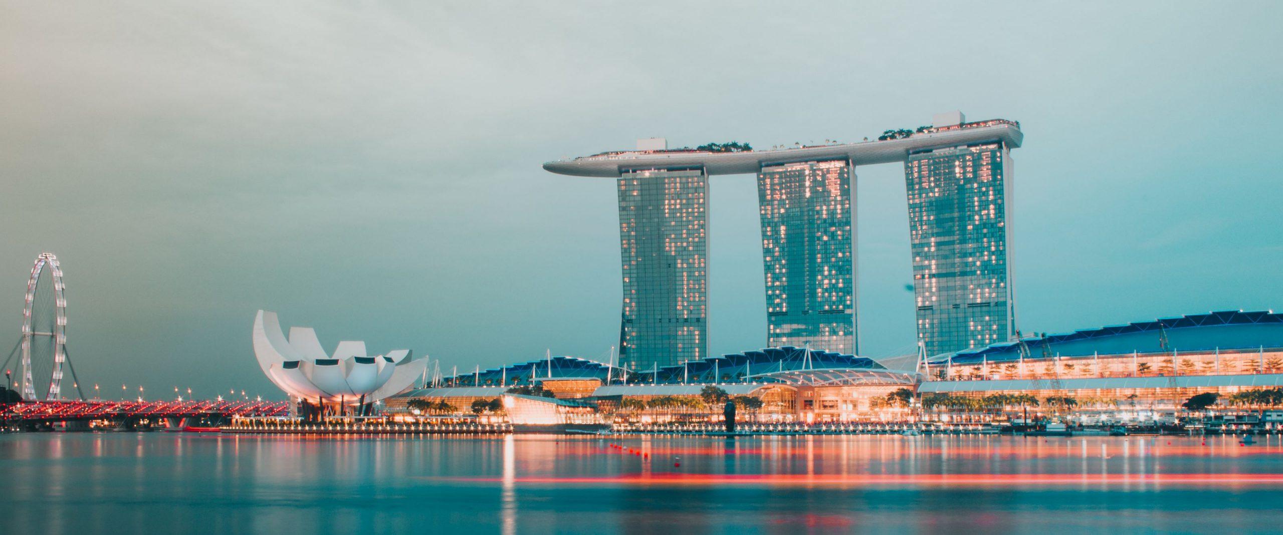 View of the Marina Bay and Marina Bay Sands Hotel lit up at dusk Singapore