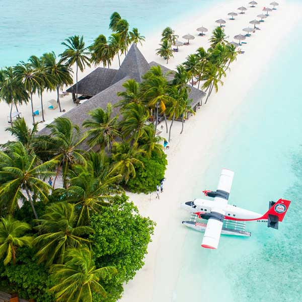 A sea plane parked up on a remote white sand beach in the maldives